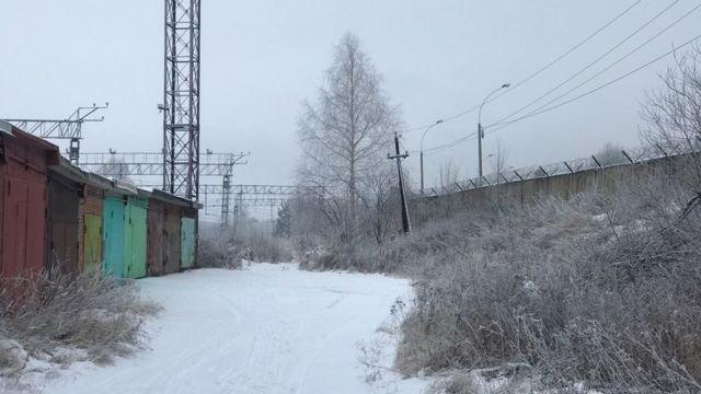 За забором находятся гаражи, вокзал и рынок