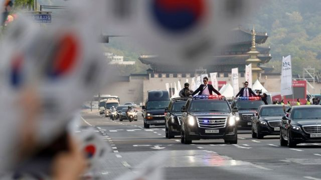 People wave South Korean flags as a convoy transporting South Korean President Moon Jae-in leaves the Presidential Blue House for the inter-Korean summit in Seoul, South Korea, April 27, 2018