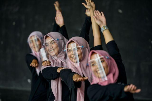 इन्डोनेशियामा नर्तकीहरू अनुहार छोपेर अभ्यास गर्दै।