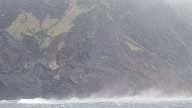 View from the sea of the island and its perilous cliffs