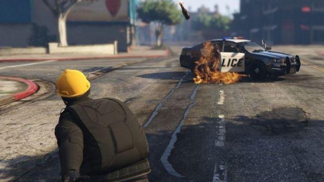 Seorang pengunjuk rasa melemparkan bom molotov ke mobil polisi di dalam gim GTA V.