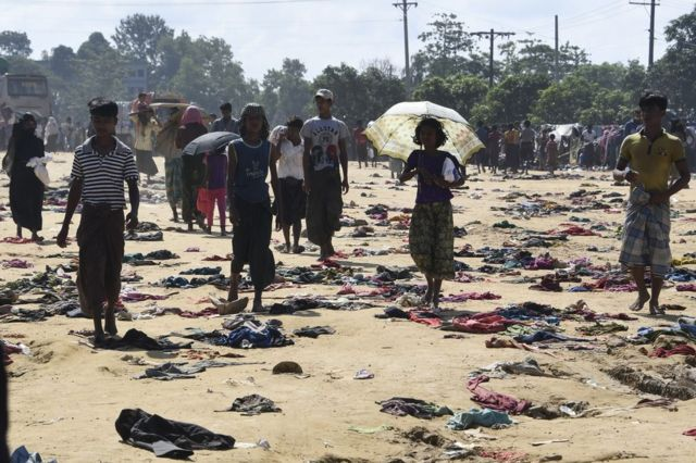 Rohingya Muslim refugees walk past discarded clothing on the ground at the Bhalukali refugee camp near Ukhia, 16 September