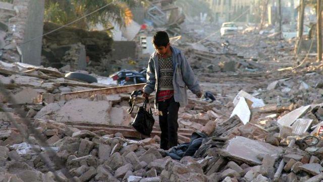 Un niño camina entre los escombros tras el terremoto de 2003 en Bam, Irán.