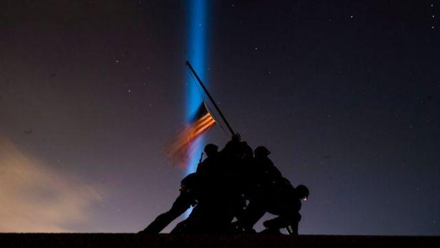 Pillars of light illuminate the sky behind the United States Marine Corps War Memorial, on the eve of the Inauguration of President-elect Joe Biden, the United States 46th president, on Tuesday, January 19, 2021, in Arlington, VA