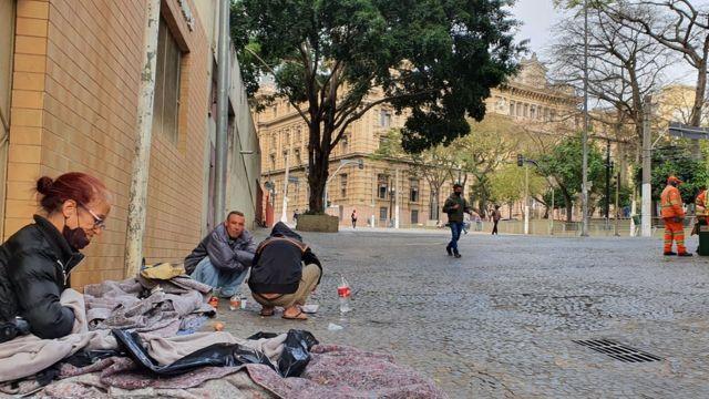 Irani Benedita de Araújo ao lado do marido (de frente) na calçada onde dormem na praça da Sé, no centro de São Paulo