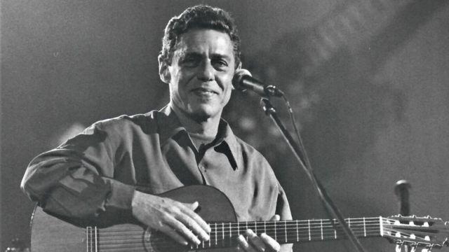 Sentado com violão, Chico sorri para foto