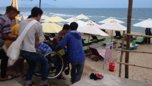Di chuyển khó khăn - chiếc xe lăn của anh Lâm cần tới 5 người khiêng để đi xuống bãi biển An Bằng, Hội An