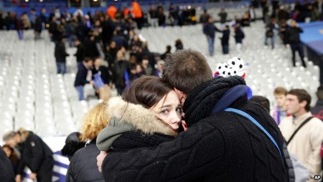 Spectators standing on pitch embrace