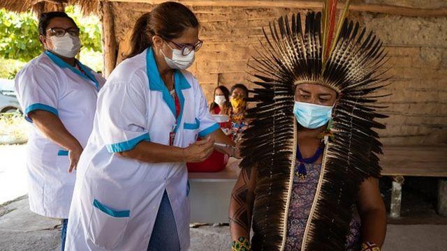 Profissional da saúde aplica vacina no braço de um indígena