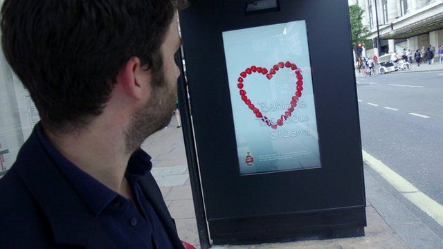 A man looking at poster which can change depending on how people respond to it