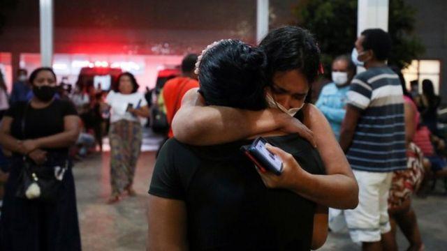 Duas mulheres abraçadas e chorando do lado de fora de hospital, com outras pessoas de máscara e ambulâncias ao fundo