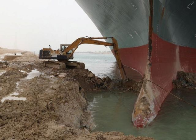 A beach bulldozer tries to remove sand and mud around the ship's case.