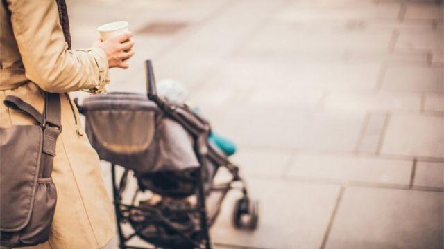 Una madres paseando un niño en un cochecito