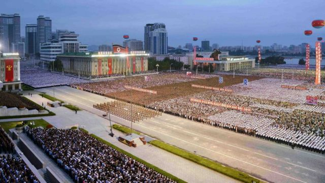 In Pyongyang, a packed square shows people wearing matching colours in neat rectangular units by the thousand, gathered in front of buildings bedecked in political banners