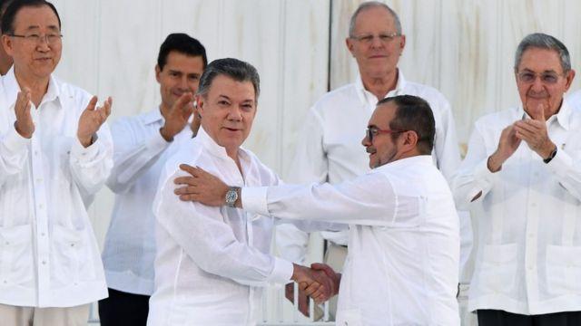 署名式で握手するサントス大統領(写真前列左)とFARCのロンドニョFARC最高司令官(26日)