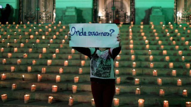 """Manifestante, com velas ao fundo, segura cartaz, onde está escrito: """"Onde erramos?"""""""