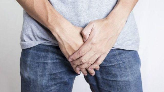 Homem de calça jeans com as mãos no pênis