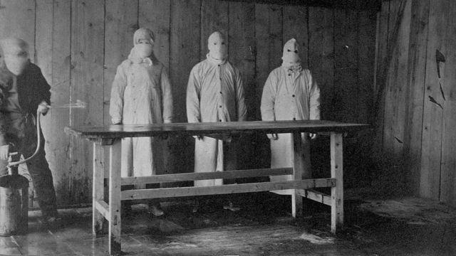 Tres hombres con batas y máscaras protectoras en el hospital de tratamiento de la peste en China, en 1910-11