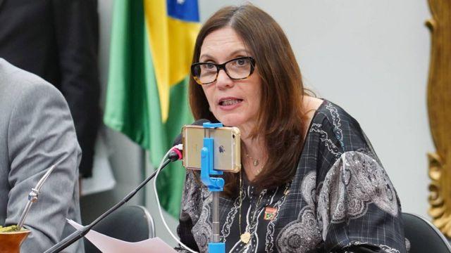 A deputada, de óculos, fala em um microfone, em frente a um celular que a grava