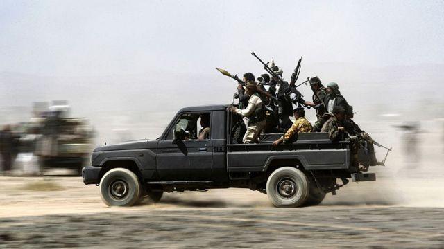 un grupo de hutíes armados en un vehículo.
