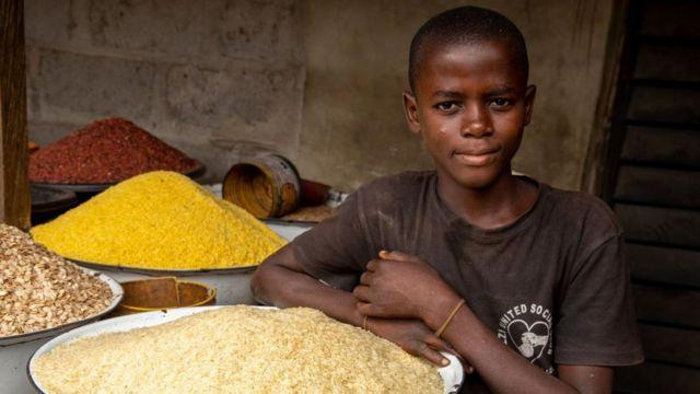 Un niño posa cerca de un abastecimiento de arroz en un mercado cerca de Lagos.