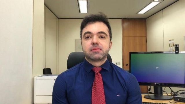 Daniel Azeredo sentado na cadeira de escritório
