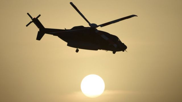 A Saudi special forces helicopter in silhouette against the sun, pictured flying during a graduation ceremony for new soldiers in May 2015