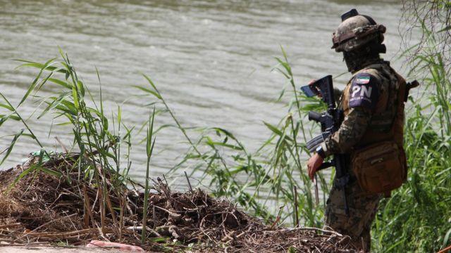 Un militar revisa las aguas de un río.