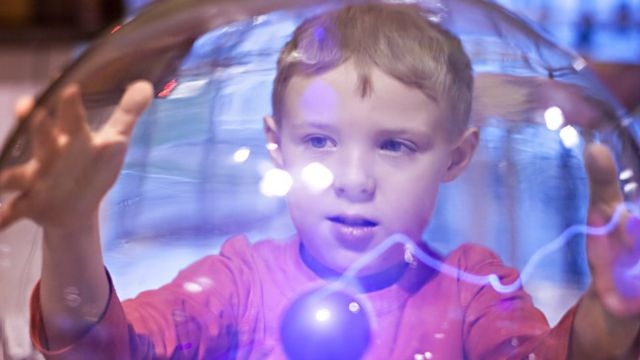 Menino brinca com bola de plasma