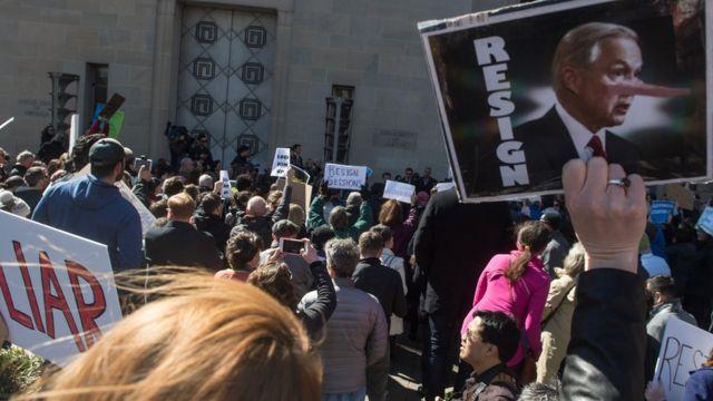 """Con carteles que dicen """"mentiroso"""" y """"renuncia"""", un grupo de manifestantes exigen la partida de Jeff Sessions frente al Departamento de Justicia en Washington D.C."""