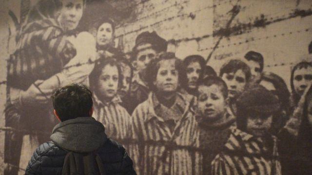 Hombre camina frente a una foto ampliada de prisioneros en un campo de concentración.
