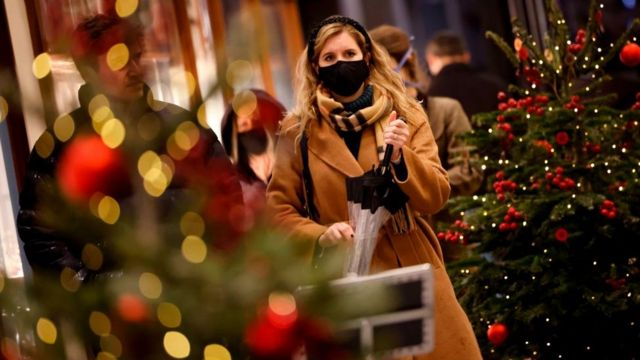 Woman with mask between Christmas trees