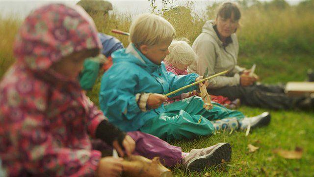 """Professora orienta crianças enquanto elas manuseiam facas em cena do filme """"Nature Play"""""""