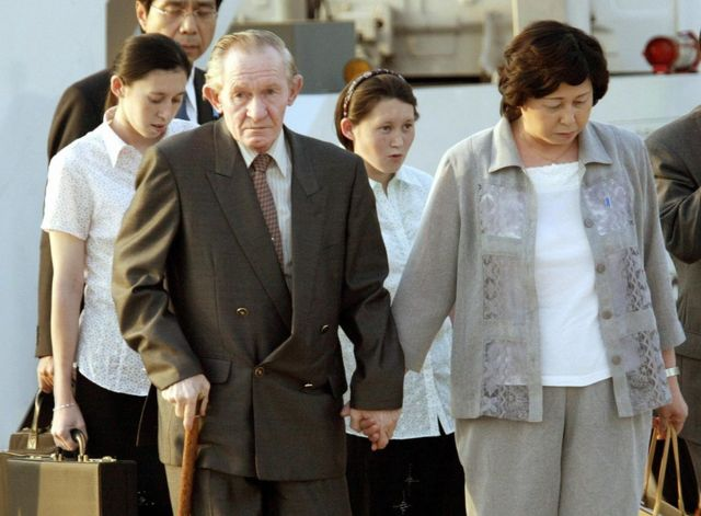 Hitomi leads her frail husband by the hand as their daughters walk behind at Tokyo international airport on 18 July, 2004