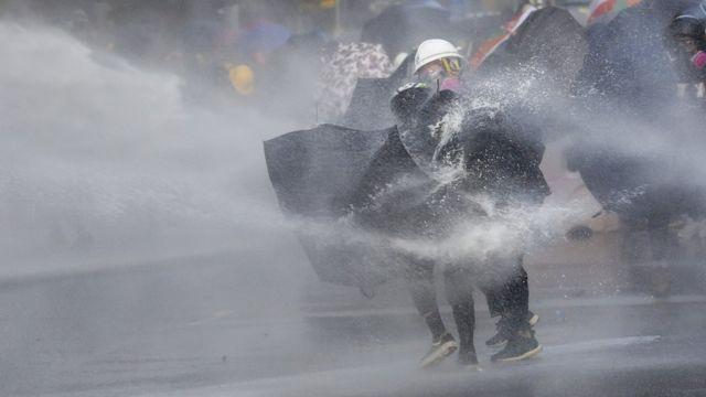 有示威者用雨傘抵擋水炮車的水柱。