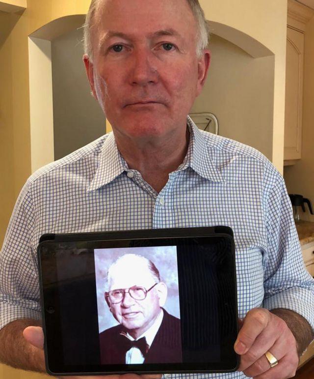 Bill Griffeth com uma foto de seu pai biológico