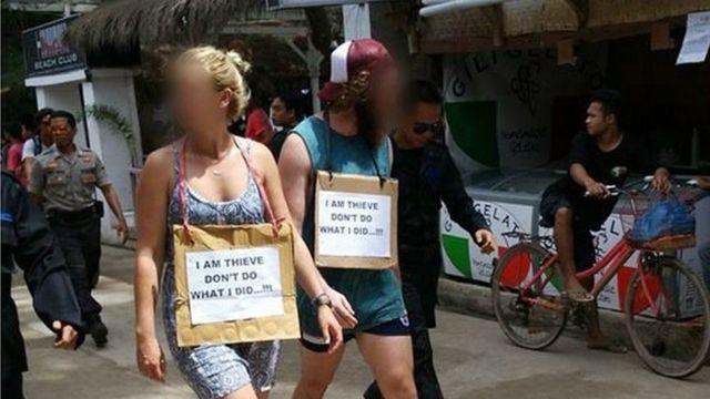 """صورة للسائحين وهما يحملان لافتة كتب عليها """"أنا سارق"""""""