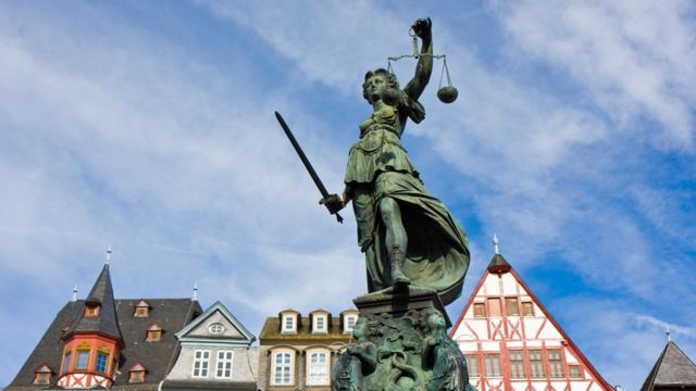 Estátua que simboliza a Justiça em frente a casas na Alemanha