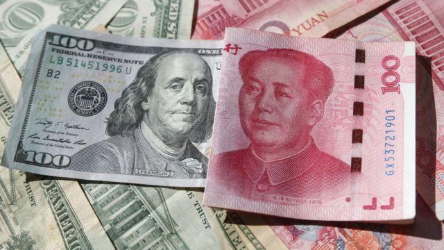 Billete de US$100 y otro de 100 yuanes.