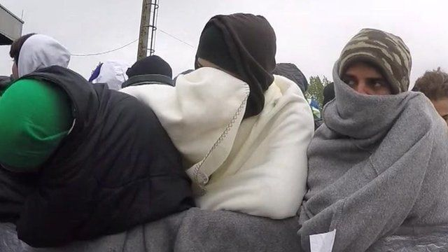 Lines of men wrapped in blankets