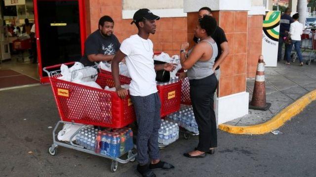عکسی از چند شهروند جاماکاییایی که بیرون یک سوپرمارکت در شهر کینگستون، پایتخت، ایستادهاند و سبدهای چرخدار خرید خود را پر از آذوقه کردهاند
