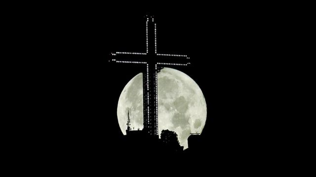 The moon rises behind the 66m (217ft) high Millennium cross in Skopje, North Macedonia
