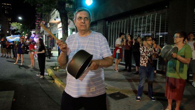 Hombre protestando con una cacerola en Buenos Aires