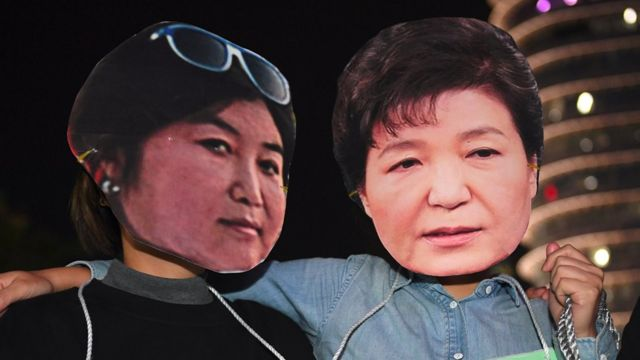 Protestors wear masks of South Korean President Park Geun-hye (right) and her confidante Choi Soon-sil (left) at a rally in Seoul, 27 October 2016