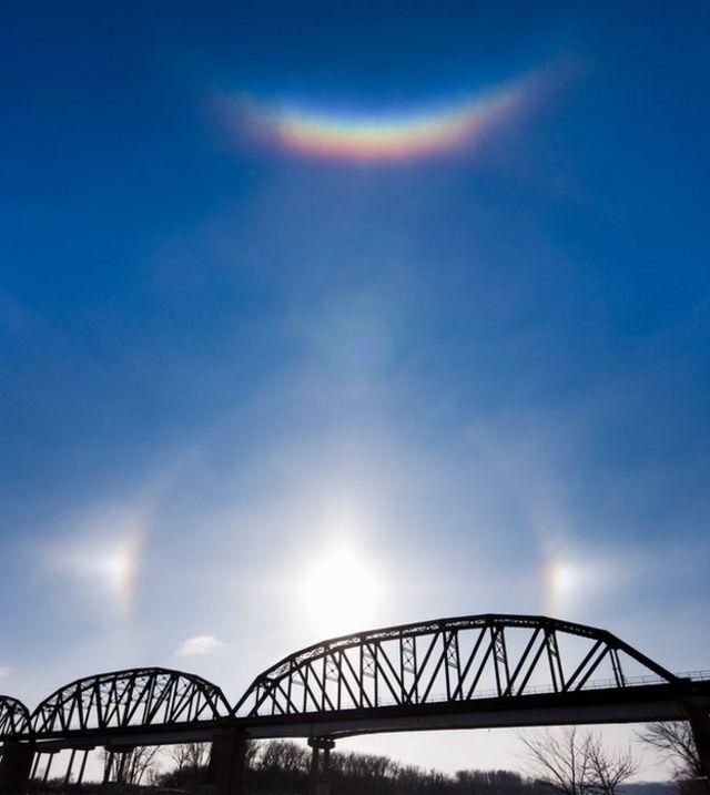 Un arco circuncenital brilla sobre el Sol y sus fantasmas sobre el río Missouri en Nebraska un frío día de enero.