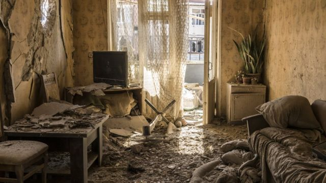 Dirt and debris covers the floor in an apartment on the top floor of a building that was shelled in Nagorno-Karabakh