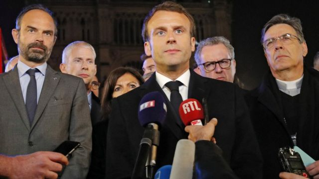 Macron perto de microfones e rodeado por assessores e membros da Igreja Católica nos arredores da Notre-Dame, durante noite