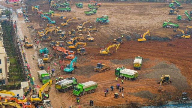 """This aerial photo on January 24, 2020 shows excavators and trucks at the construction site of a new hospital being built to treat patients from a deadly virus outbreak in Wuhan in China""""s central Hubei province"""