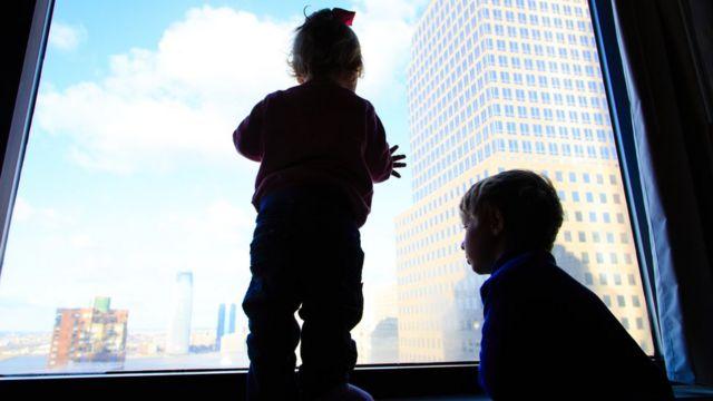Duas crianças olhando cidade da janela de um apartamento