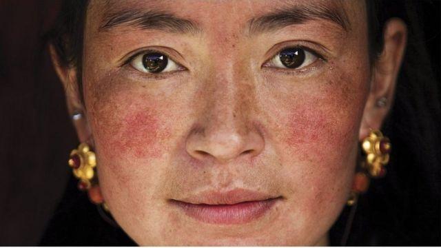 """攝影師米哈艾拉在鄉村遇到了有兩個孩子的藏族母親。米哈艾拉說,""""她當時戴著首飾在打掃房屋""""。"""